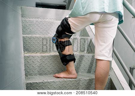 Patient with knee brace in moving upstairs