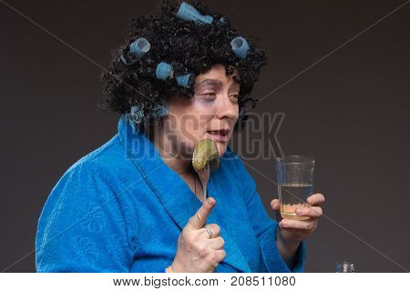 Lonely mature fat woman alcoholic drinks vodka from glasses and wine glasses and snack cucumber and dried fish