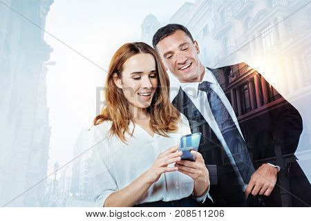 Inquisitive colleague. Funny friendly young man looking at the screen oh a smart phone in his colleagues hands and smiling