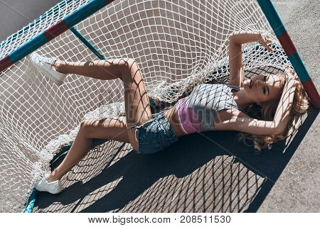Gorgeous sensual model. Top view of attractive young woman in casual wear looking away while lying in the goal post outdoors