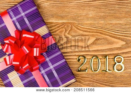 Gift with a red bow and figures 2018 on a wooden background
