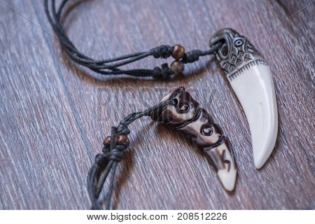 Big bear tooth and bone pendants carved from siberian deer on a brown background