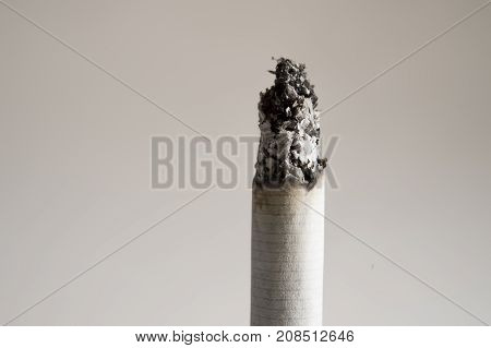 close up burning ash on cigarette isolated on clear background in unhealthy dangerous habit of tobacco and smoking addiction concept