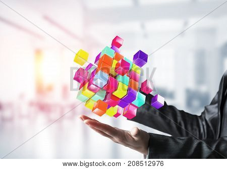 Closeup shot of business woman hands holding multiple cubes of different colours in hands with sunlight on office background. Mixed media.