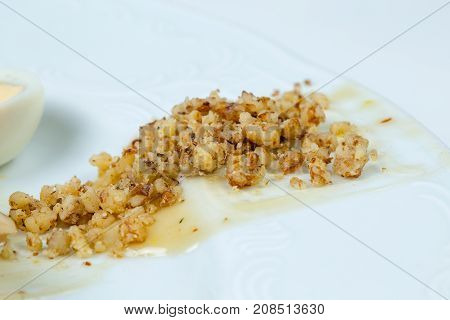 Crushed walnuts with sauce on white background