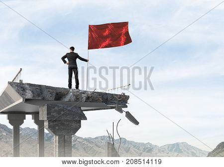 Rear view of confident businessman in suit holding flag in hand while standing on broken bridge with cloudly skyscape and nature view on background. 3D rendering.