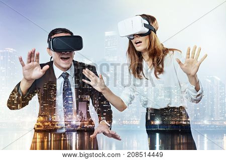 Virtual reality. Enthusiastic young colleagues experiencing incredible feelings while testing virtual reality glasses
