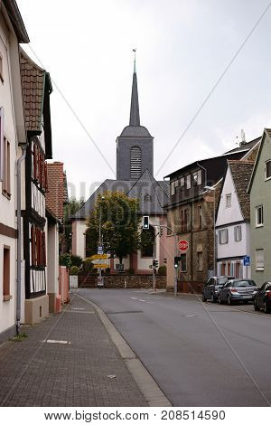 BISCHOFSHEIM, GERMANY - SEPTEMBER 23: The tower of the Evangelical Church at the end of a main road with adjacent residential buildings on September 23, 2017 in Bischofsheim.