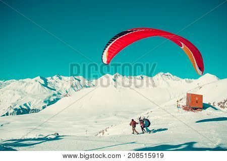 Two paraglider tandem take a run before fly. Colorful parachute. Active lifestyle Extreme hobbies. Paragliding Georgia. Adventure travel. Winter mountain landscape. Entertainment concept. Adrenalin