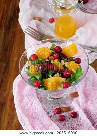 Fruit salad with orange pieces, cranberries, date fruits and arugula in a glass salad bowl