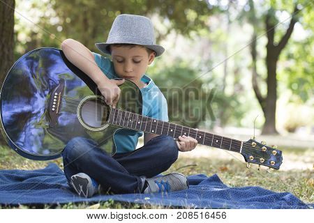Portrait Of A Little  Boy Sitting In A Park And Playing A Guitar