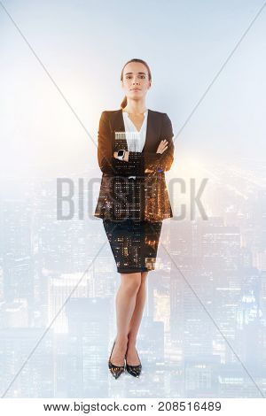 Serious woman. Determined serious elegant director standing with her arms crossed on the chest