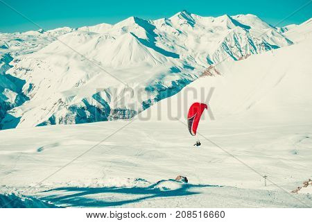 Paraglider tandem flying over ski resort. Active lifestyle Extreme hobbies. Paragliding explore Georgia. Adventure travel. Winter mountain landscape. Fearlessness concept. Freedom. Text space.