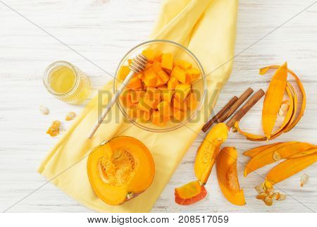 Pumpkin Cut Into Pieces In A Bowl And Honey On A White Table
