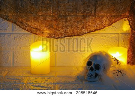 Halloween decoration candles and horror skull on wall background