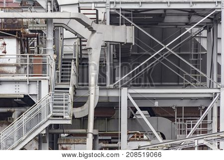 weathered rundown industrial scenery with old corroded steel girders stairs and metal tubes