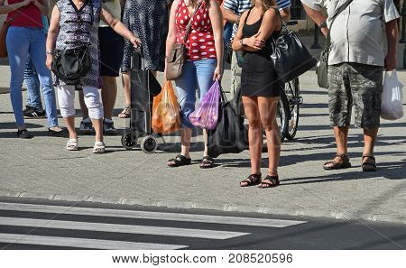 Pedestrians waiting at the road crossing in the city