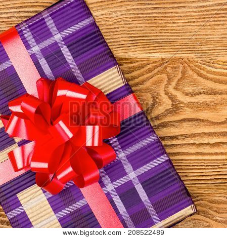 Gift with a red bow on a wooden background