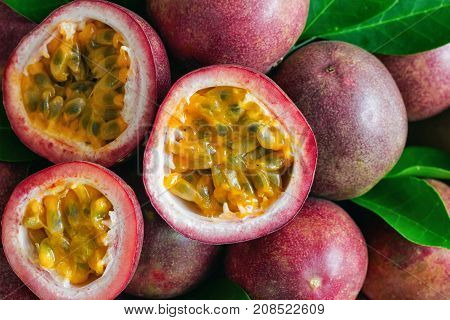 Fresh passion fruit on wood table in top view flat lay for background or wallpaper. Ripe passion fruit so delicious sweet and sour. Close up on a half of passion fruit in macro concept. Passion fruit is tropical fruit.