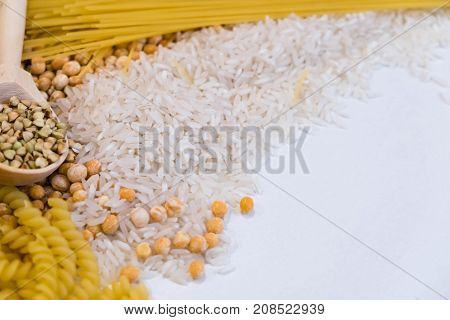 Set of products with complex carbohydrates on white background. wooden spoon, a range of cereals, pasta. Gluten free flour and cereals millet, green buckwheat, basmati rice, up view