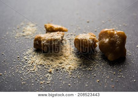 Asafoetida cake and powder or Hing or Heeng which is an important ingredient in Indian food recipes with big wooden spoon and mortar, selective focus