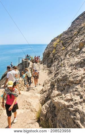 New World, Crimea - 12 July, Groups of tourists on a rocky path, 12 July, 2017. Travel along the coast along the path of Prince Golitsyn.