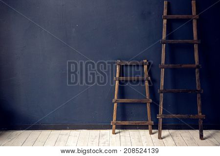 two wooden ladders stand at the blue wall on white floor indoors