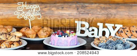Birthday cakes and muffins with wooden greeting signs on rustic background. Wooden sing with letters Happy Birthday, Baby and holiday sweets