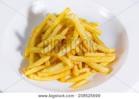 close up on crispy french fried on white plate. junk food