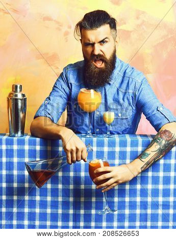 Bearded man long beard. Brutal caucasian dissatisfied hipster with moustache in shirt doing cocktail or beverage and alcohol shot with bar stuff on blue checkered plaid on colorful texture background