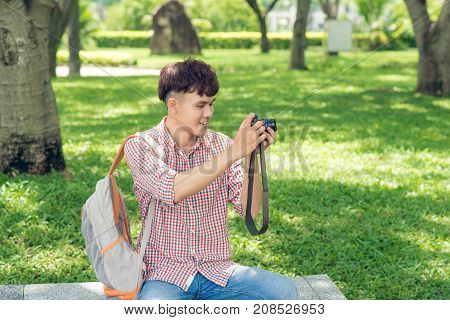Young smiling man taking picture while walking in park