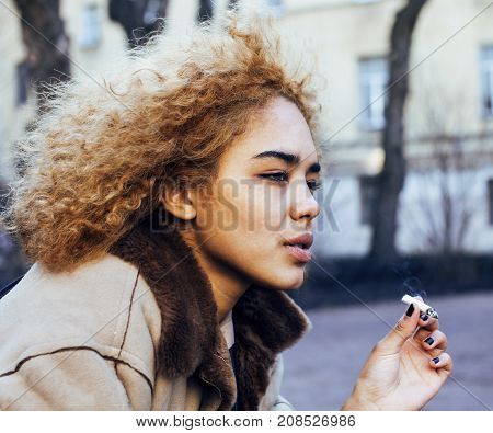 young pretty girl teenage outside smoking cigarette, looking like real junky, social issues concept close up