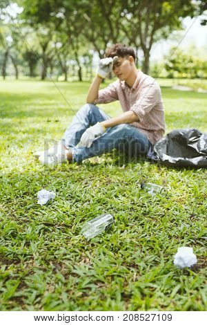 Tired man after crouching to waste in the park. Focus on waste.