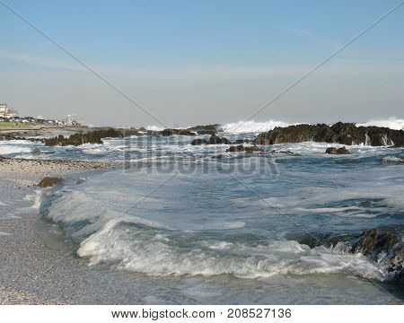 WINTER SEASCAPE, WITH WAVES SMASHING AGAINST SOME ROCKS AND SHOOTING UP INTO THE AIR