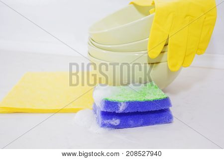 Several colorful plates, kitchen sponges. Dishwasher concept