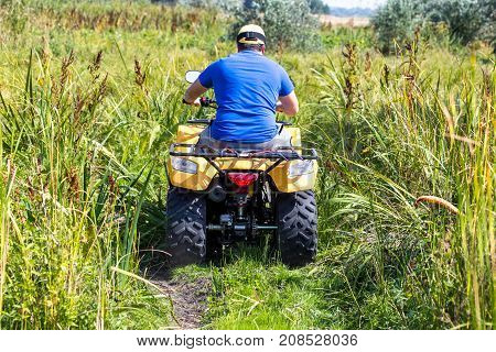 Caucasian man in sport protective goggles riding an ATV quad bike over rough terrain between high grass bushes. Adventure activity concept.