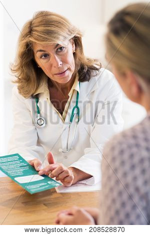 Doctor Discussing Leaflet With Female Patient In Surgery