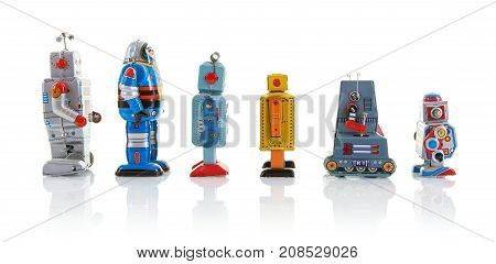 SWINDON UK - OCTOBER 1 2017: Row of old clockwork tin robots in a line on a white background