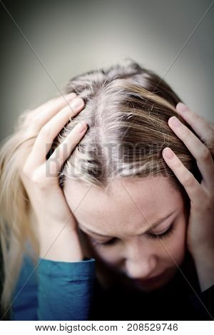 Young Woman Suffering From Depression With Head In Hands