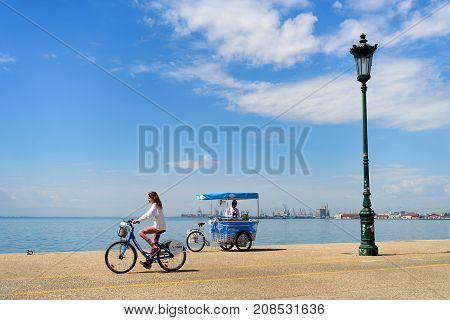 Thessaloniki, Greece - April 14, 2017 : Young girl riding an iBike at the seafront of the northern Greek city of Thessaloniki with ice cream vendor cart in background