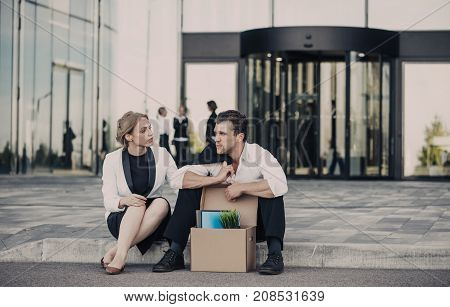 Fired business man sitting frustrated and upset on the street near office building with box of his belongings. He lost work. Business woman comforts and encourages him