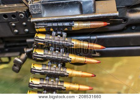 Cartridges in machine-gun belt on diffuse background