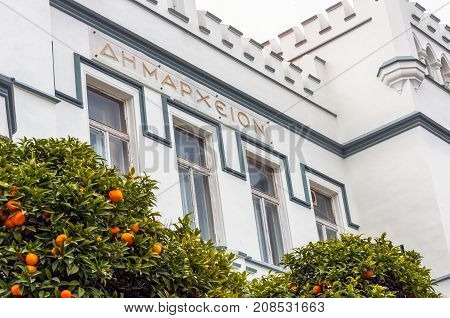 Kavala, Greece - April 8, 2011 : White facade of the Town Hall of Kavala and orange tree in front. Foreign text translates as town hall or municipality