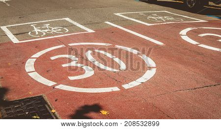White Paint On A Red Road Indicating Presence Of A Bicycle And Forbidden To Exceed The Speed Of 30