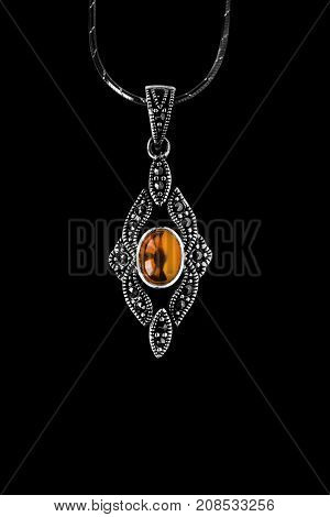 Vintage silver amber pendant on a chain isolated over black
