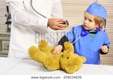 Man And Boy Hold Stethoscopes On Wooden Background.
