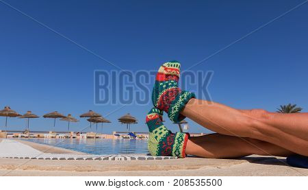 Christmas sock on palm tree at exotic tropical beach. Holiday concept for New Years Cards. Christmas sock on a sunlit legs of attractive women in background pool and palm trees