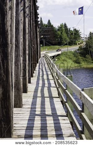 Vertical long view of a wooden walkway across a bridge with the Acadian Flag of New Brunswick blowing in the wind against a blue sky on a sunny afternoon in August.