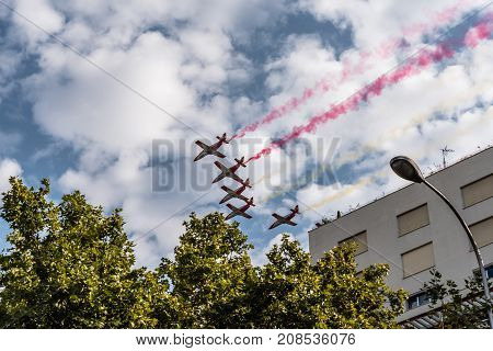 Madrid Spain - October 12 2017: Aguila Patrol jet fighters flying with coloured smoke in Spanish National Day Parade. Several troops take part in the army parade for Spain's National Day.