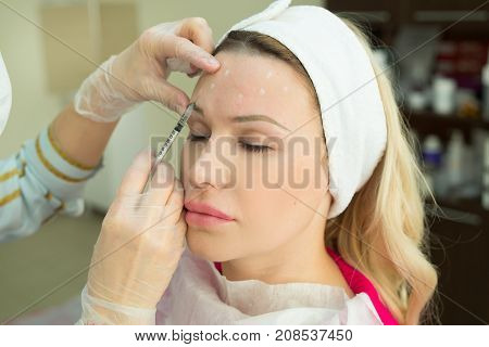 Beautiful young girl of European appearance on the procedure of injecting injections in the salon of cosmetology